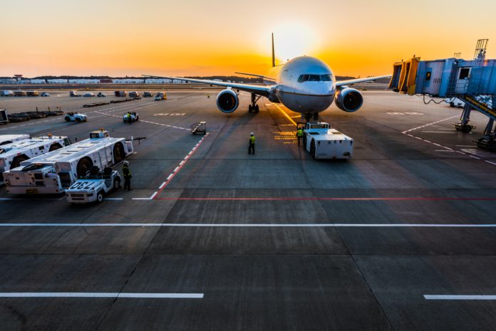 An airplane sits on the tarmac with luggage tugs nearby